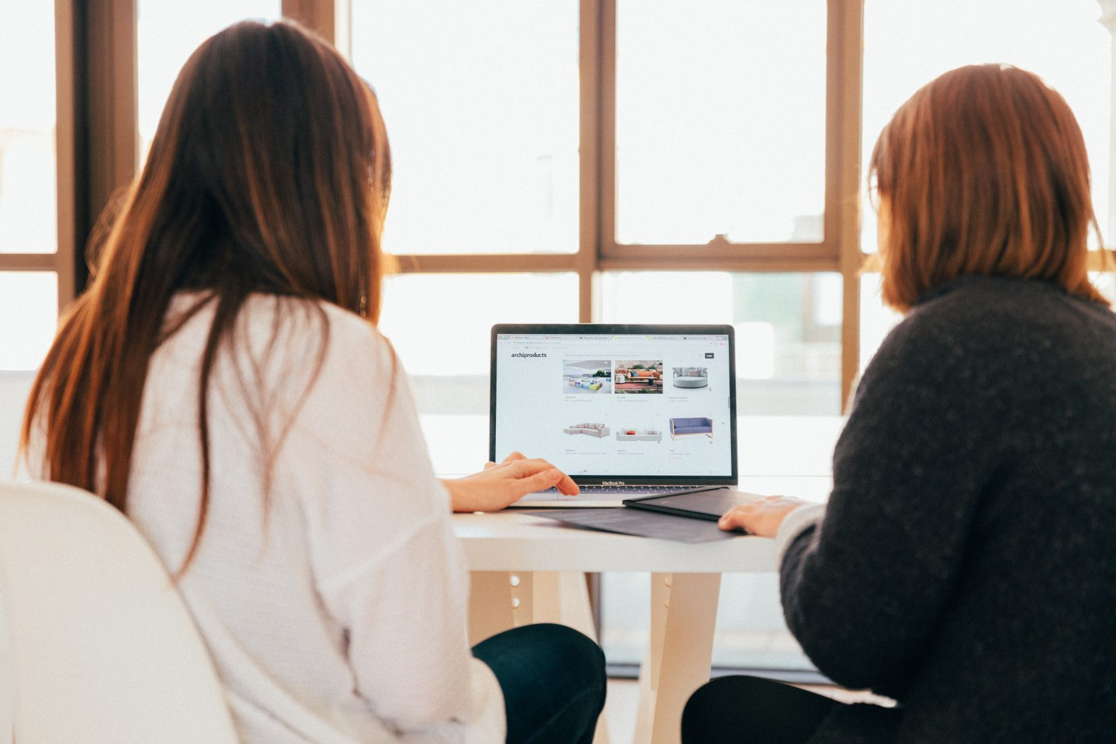 two women talking while looking at laptop computer