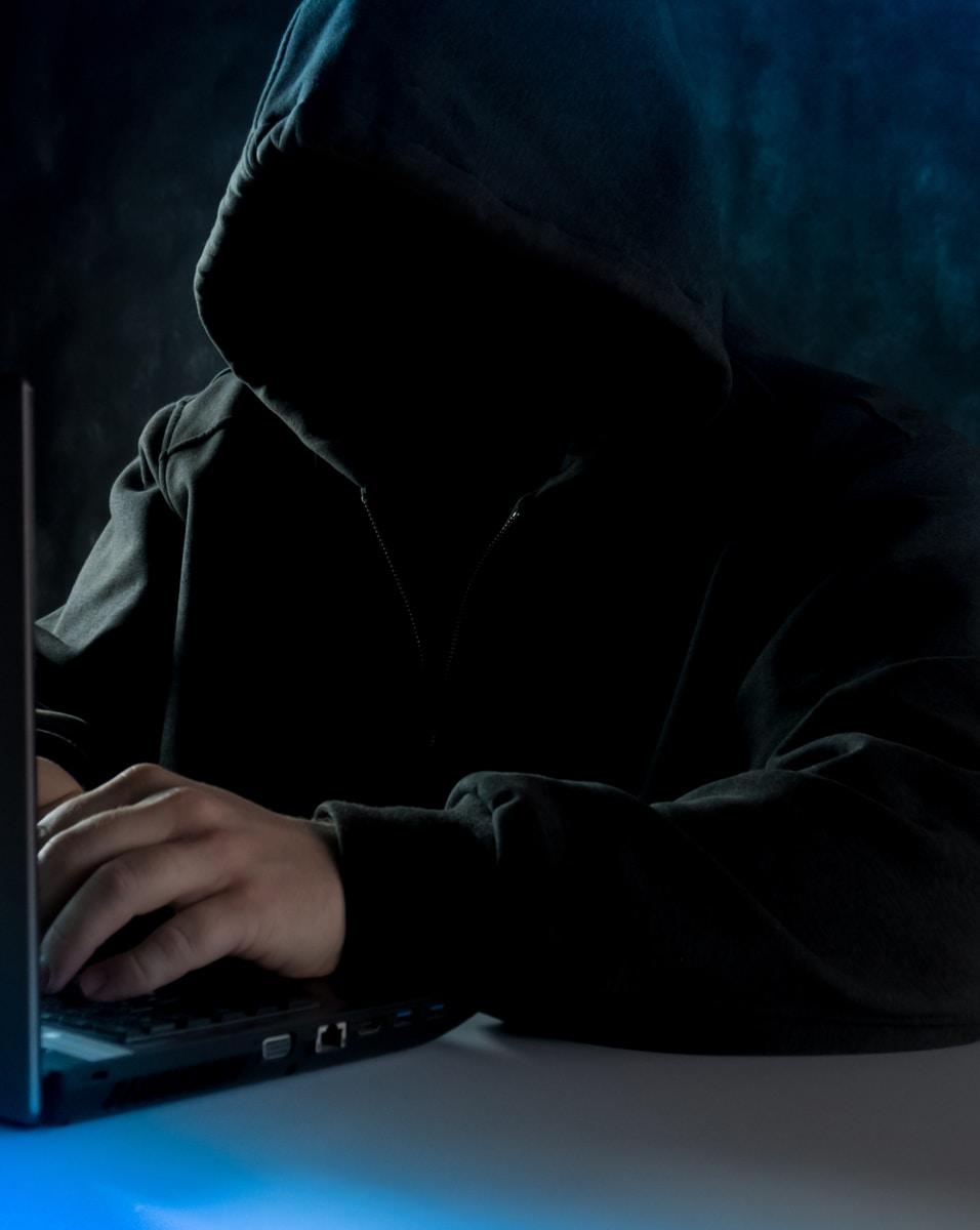 person in black hoodie using laptop computer